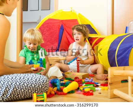 Young mother and children playing with  toys in  interior - stock photo
