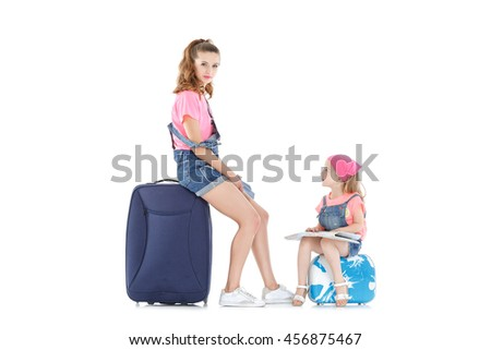 young mother and cute little daughter waiting plane . a woman looks at the scoreboard, and the child is studying the tourist map isolated on white background