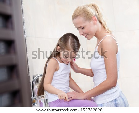 Young mother and daughter communicate in bathroom - stock photo