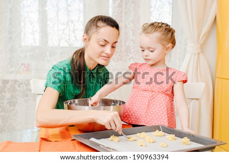 young mother and daughter cooking in the kitchen - stock photo