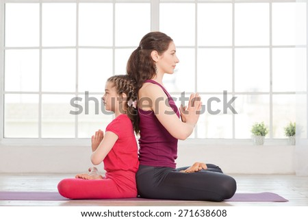 Young mother and daughter doing yoga exercise and sitting back to back in fitness studio with big windows on background - stock photo