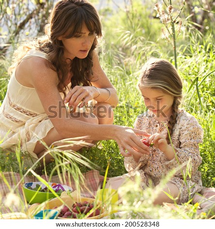Young mother and daughter enjoying a picnic together in a dreamy green field, eating strawberries with mom crouching to help the young girl. Family activities and healthy eating lifestyle, outdoors. - stock photo