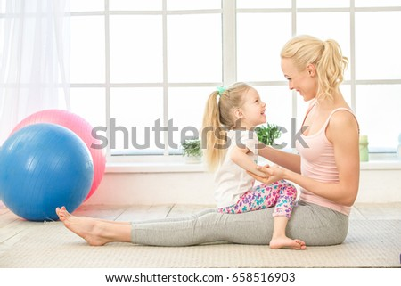 Young mother and daughter exercise together indoors