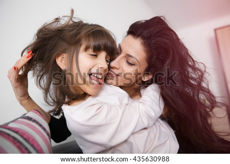 Young mother and daughter having fun, kiss and hugs on the sofa at home in white lit room against the window. Smooth morning light, casual style - concept of happy family living and lifestyle - stock photo