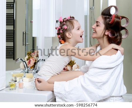 Young mother and daughter in curlers in a bath room happy smiling hugging each other family skin care concept in bathroom