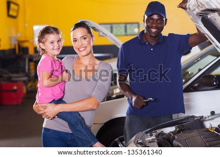 young mother and daughter in garage with auto mechanic - stock photo