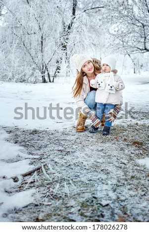 Young mother and daughter laughing for a walk in winter forest - stock photo