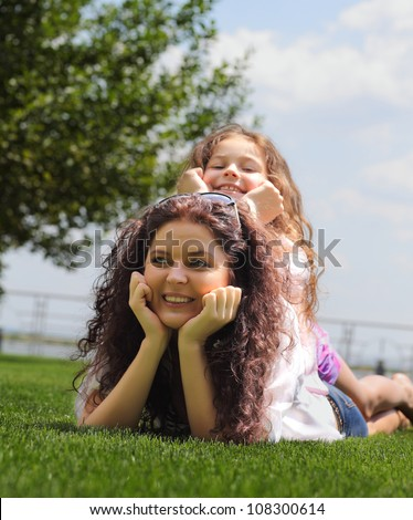 Young mother and daughter laying on the grass - stock photo