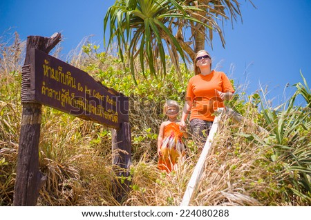 Young mother and daughter on trekking road on tropical island - stock photo