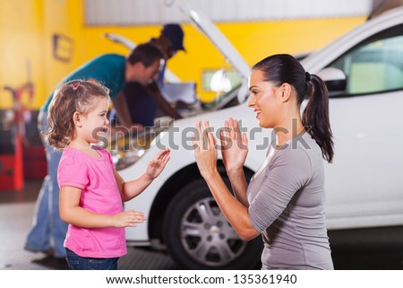 young mother and daughter playing a game while waiting in garage - stock photo