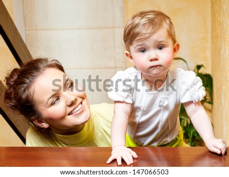 Young mother and daughter playing at home