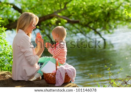 Young mother and daughter playing near the lake - stock photo
