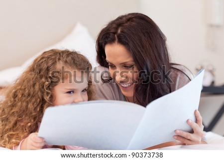Young mother and daughter reading a book together