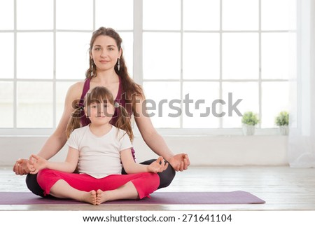 Young mother and daughter sitting in lotus position and doing yoga exercise in fitness studio with big windows on background - stock photo