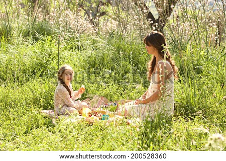 Young mother and daughter sitting relaxing together in a sunny field of long grass and flowers having a picnic and enjoying a summer holiday in nature. Eating and relaxing family activities lifestyle. - stock photo