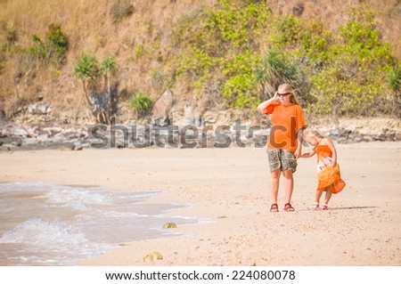 Young mother and daughter walk along island beach - stock photo