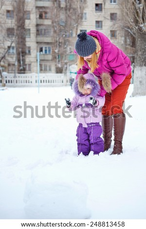 Young mother and daughter walking on clean snow in the park. Young family on the walk. - stock photo