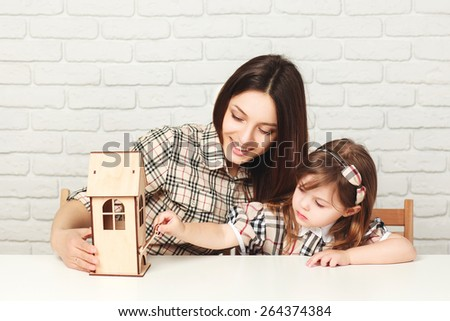 Young mother and daughter with little wooden house. Family, investment and payment concept. Girl trying to open house with wooden key. - stock photo