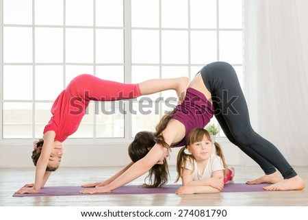 Young mother and daughters doing yoga exercise in fitness studio with big windows on background - stock photo