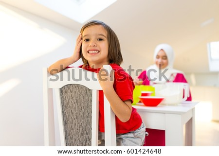 Young mother and happy playful son making muffins in kitchen