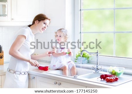 Young mother and her adorable curly toddler daughter washing vegetables together in a kitchen sink getting ready to make salad for lunch in a sunny white kitchen with a big garden view window - stock photo