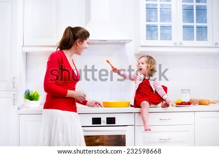Young mother and her adorable daughter, cute funny toddler girl in a red dress, baking a pie together preparing healthy lunch in a white sunny kitchen  - stock photo