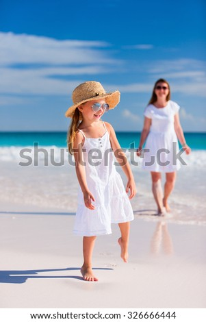 Young mother and her adorable little daughter on summer beach vacation - stock photo