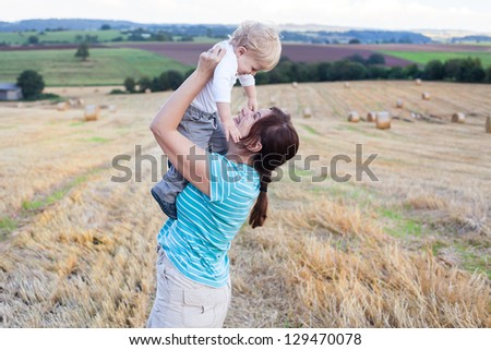 Young mother and her adorable little son having fun in straw field, Germany. - stock photo