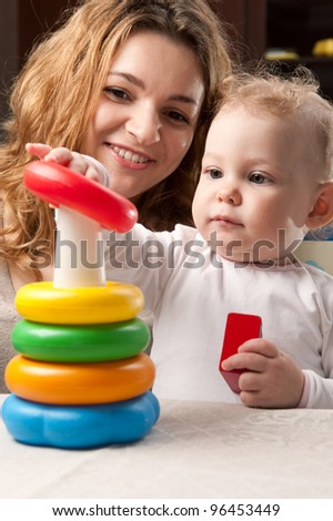 Young mother and her baby daughter building toy pyramid tower - stock photo