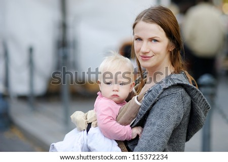 Young mother and her baby girl in a baby carrier - stock photo