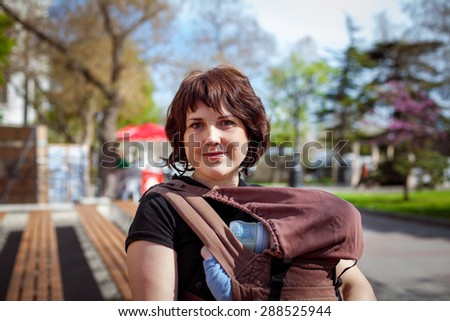Young mother and her baby in a baby carrier - stock photo