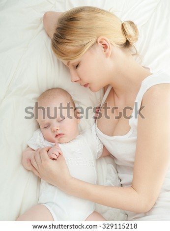 Young mother and her baby, sleeping in bed. Mother and baby. Happy family. - stock photo