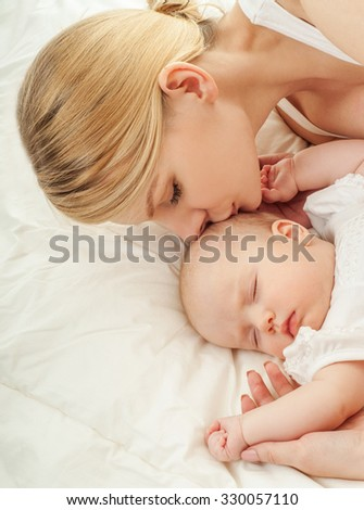 Young mother and her baby, sleeping in bed. Mother and baby. Happy family.