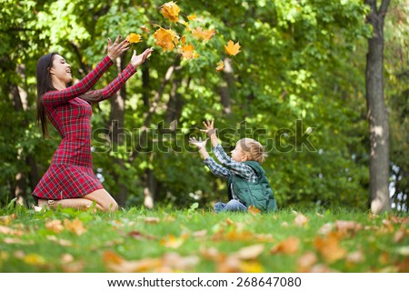 Young mother and her child throwing yellow maple leaves in the air in park