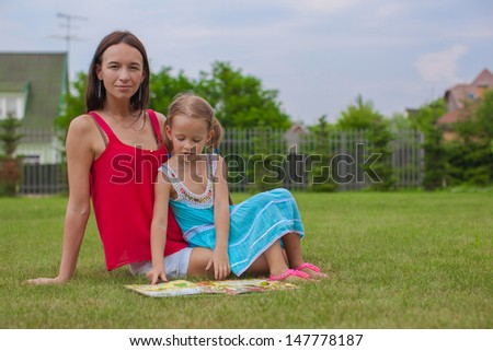 young mother and her cute daughter reading a book and enjoying the holiday