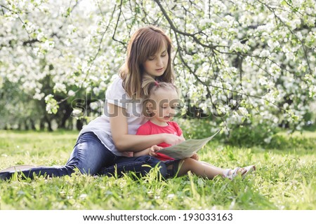 young mother and her cute daughter reading book and enjoying holiday