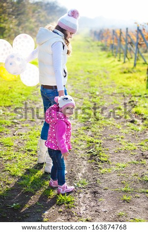 Young mother and her cute girl have fun in autumn vineyard