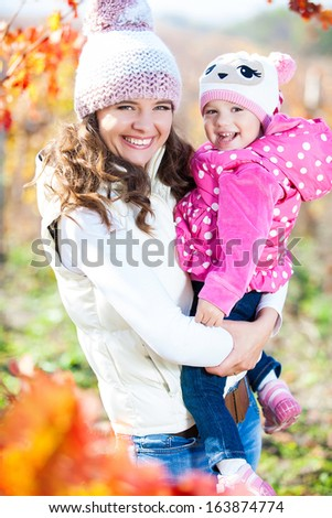 Young mother and her cute girl have fun in autumn vineyard - stock photo