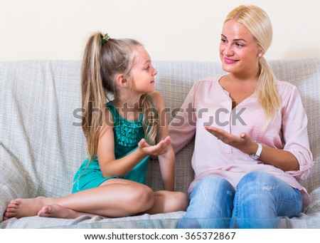 Young mother and her cute little daughter talking and laughing at home