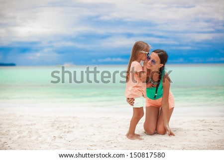 Young mother and her cute little girl whispering on the white beach - stock photo