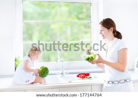 Young mother and her cute toddler daughter cooking together a healthy salad for lunch in a beautiful sunny kitchen with a big window  - stock photo