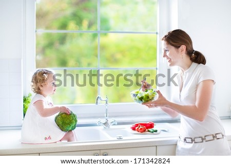 Young mother and her cute toddler daughter cooking together in a beautiful sunny kitchen with a big window - stock photo