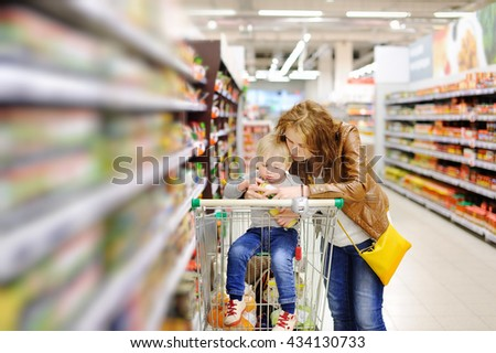 Young mother and her cute toddler son in a food store or a supermarket