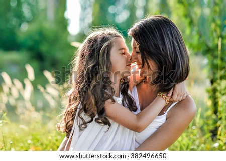 young mother and her daughter at the wheat field on a sunny day, summer - stock photo