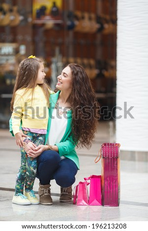 Young mother and her daughter doing shopping together. Shopping mall. Shopping bags. - stock photo