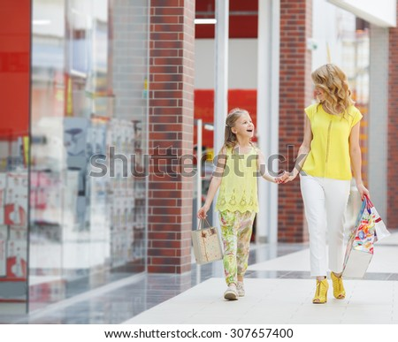 Young mother and her daughter doing shopping together. Woman with child on shopping in shopping mall with bags - stock photo