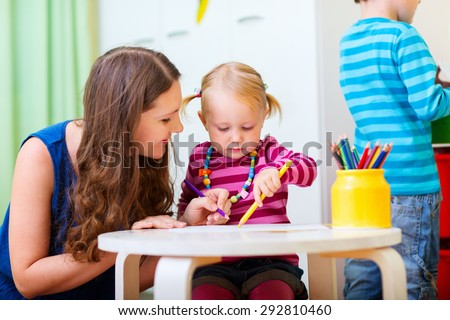 Young mother and her daughter drawing together. Also perfect for kindergarten daycare context. - stock photo