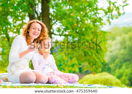 young mother and her daughter eating apples in the park