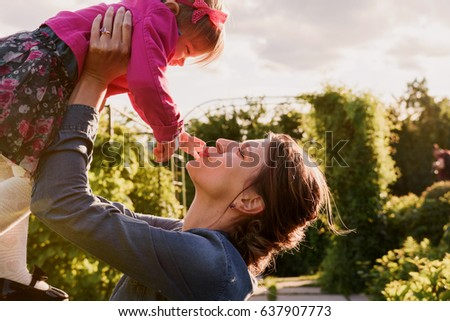 Young mother and her daughter resting in the park. Soft sunset light. Mom kiss the baby. Mothers day