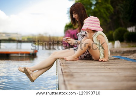 Young mother and her daughter sitting on a pier - stock photo